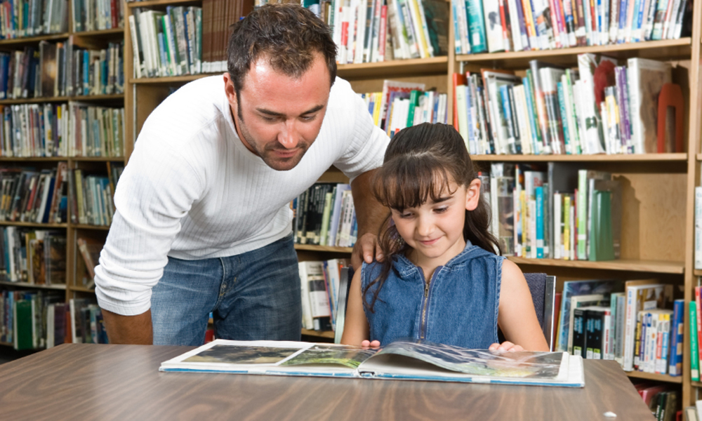 Male teacher helping girl read in library