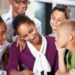 Diverse group of students gather around woman teacher