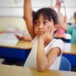Girl timidly raising hand in class